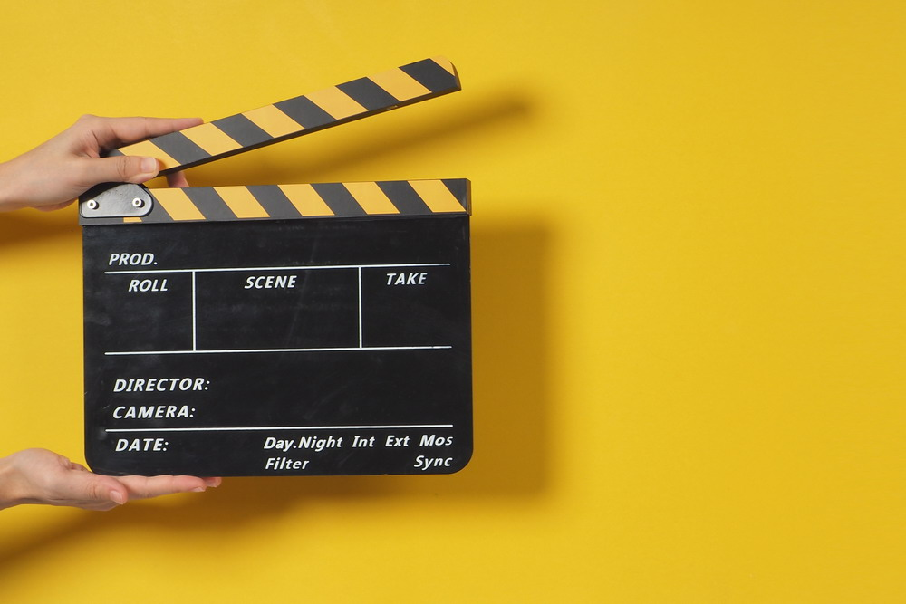 Hand is holding clapper board or movie slate.It is used in video production and film industry on yellow background.